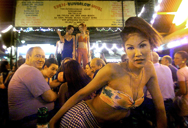 """ORG XMIT: 532401_1.tif (FILES) File picture dated 21 February 2002 shows a young Thai ladyboy, or transvestite, smiles and dances 'her' way through a crowd of foreign tourists as others dance on a stage (background) at Phuket's garishly overdeveloped Patong Beach, where ladyboys still pose for photos for wide-eyed tourists at """"Soi Katoey"""", or """"Transvestite Street"""", one of its most popular late-night attractions. A prominent Thai senator proposed Tuesday that the nation's transsexuals be fully recognised as women and allowed to legally adopt the female designations """"Miss"""" or """"Mrs"""". Wallop Tangkananurak, a noted social activist, said he was """"testing the waters"""" on the idea which was designed in part to shield men who had undergone sex-change operations from discrimination and abuse. AFP PHOTO/Stephen SHAVER"""