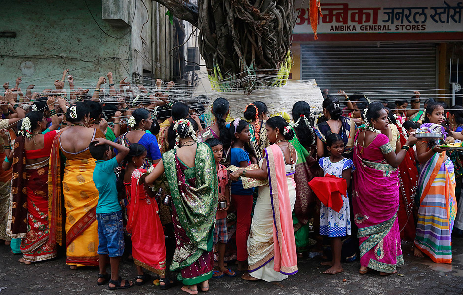 Indian Hindu married women tie cotton threads around a Banyan tree as they perform rituals on the occasion of Vat Savitri festival in Mumbai, India, Sunday, June 19, 2016. Vat Savitri is celebrated on a full moon day where women pray for the longevity of their husbands. (AP Photo/Rafiq Maqbool) ORG XMIT: DEL106