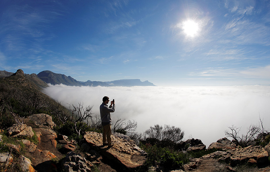 A visitor takes photographs from the scenic Ou Kaapse Weg as seasonal fog covers the city in Cape Town, South Africa, May 29, 2016. REUTERS/Mike Hutchings ORG XMIT: GGGMSH03