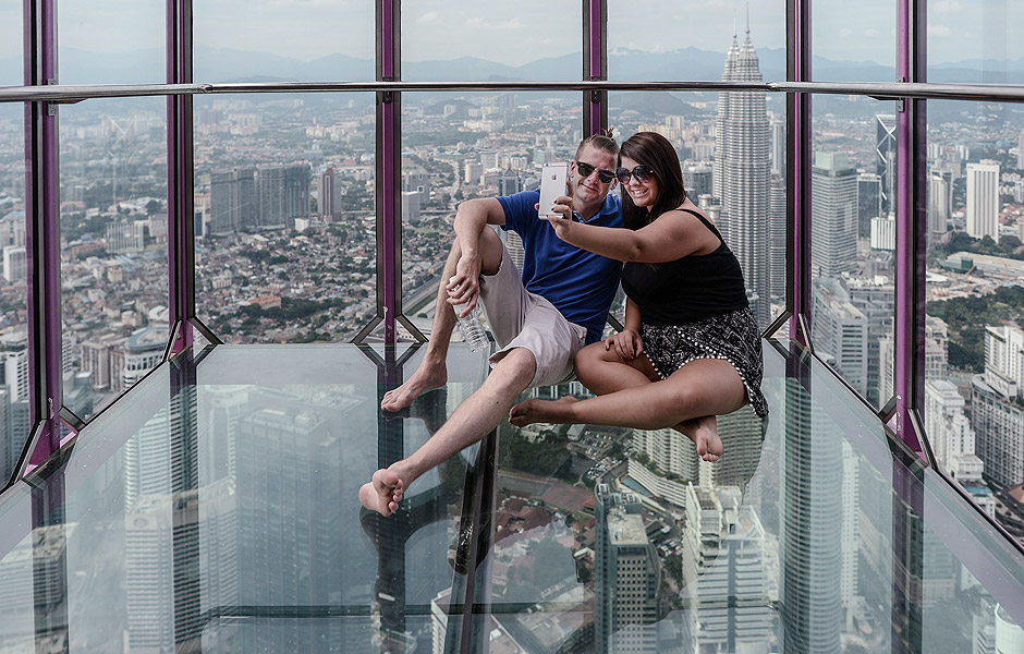 Mohammed Ehtsham (L) and Maham Ehtsham (R) from England take pictures with the panoramic view of the city from the Sky Box at KL Tower, the world's seventh tallest telecommunications tower, in Kuala Lumpur on May 24, 2016. Officially opened on May 20, the Sky Box has been the latest attraction for tourists arriving to the Malaysian capital. It stands 300 metres above ground and can fit six people at any one time, and offers spectacular views of the Kuala Lumpur skyline, including the iconic Petronas Twin Towers. / AFP PHOTO / MOHD RASFAN ORG XMIT: MRN625