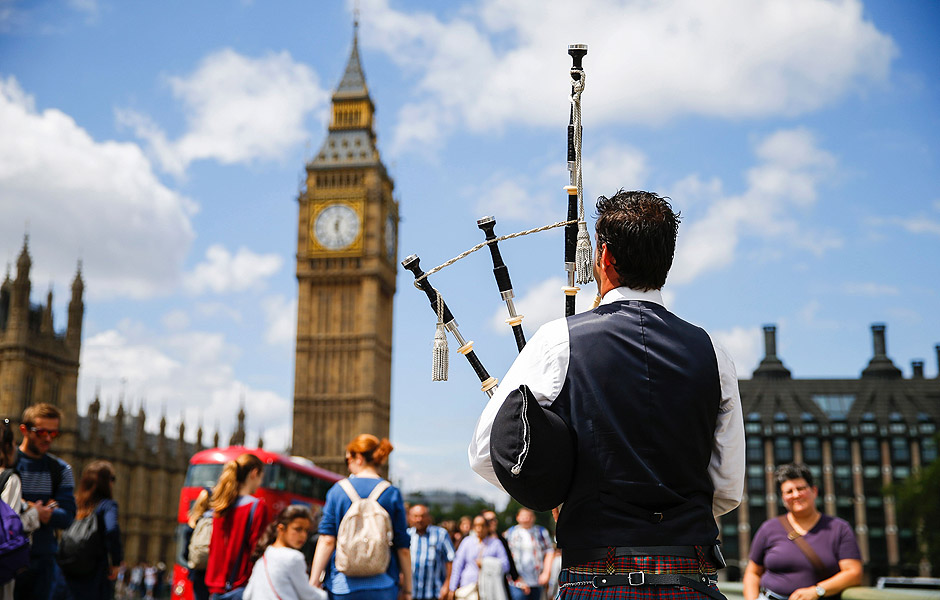 A Scottish piper plays for tourists in front of the Queen Elizabeth Tower (Big Ben) and The Houses of Parliament in central London on June 26, 2016. Britain's opposition Labour party plunged into turmoil Sunday and the prospect of Scottish independence drew closer, ahead of a showdown with EU leaders over the country's seismic vote to leave the bloc. Two days after Prime Minister David Cameron resigned over his failure to keep Britain in the European Union, Labour leader Jeremy Corbyn faced a revolt by his lawmakers who called for him, too, to quit. / AFP PHOTO / Odd ANDERSEN