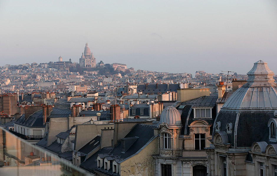 A general view shows city rooftops with chimney stacks of residential apartment buildings in Paris February 6, 2015. A campaign has been launched to grant the roofs of Paris as World Heritage status recognised by UNESCO, by the mayor of the capital's 9th district and a support committee. This campaign is also a demand to protect them and promote them as a tourist attraction. In the background, the Sacre Coeur Basilica on Montmartre. REUTERS/Philippe Wojazer (FRANCE - Tags: CITYSCAPE TRAVEL SOCIETY) ORG XMIT: PHW10