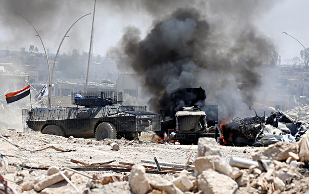 An Iraqi military truck set afire after it was hit by IS militants in Mosul, Iraq