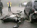 Man takes pictures of a motorcycle destroyed in the accident; the pile-up involved 50 accidents says Road Police