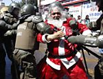 Manifestante vestido de Papai Noel  preso pela polcia durante protesto contra a o poltica da educao do Chile, em Santiago