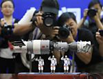 Fotgrafos tiram foto de modelo em miniatura da nave espacial Shenzhou-9 e trs astronautas chineses aps entrevista coletiva no Centro de Lanamento de Satlites Jiuquan, na provncia de Gansu (China)