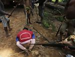 Ka'apor Indian warriors stand over a logger they captured and tied up during a jungle expedition to search for and expel loggers from the Alto Turiacu Indian territory, near the Centro do Guilherme municipality in the northeast of Maranhao state in the Amazon basin