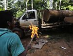 A Ka'apor Indian warrior gets ready to set fire to a logging truck they discovered during a jungle expedition to search for and expel loggers from the Alto Turiacu Indian territory, near the Centro do Guilherme municipality in the northeast of Maranhao state in the Amazon basin