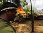 A Ka'apor Indian warrior stands near a burning logging truck during a jungle expedition to search for and expel loggers from the Alto Turiacu Indian territory, near the Centro do Guilherme municipality in the northeast of Maranhao state in the Amazon basin