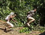 A Ka'apor Indian warrior (L) chases a logger who tried to escape after he was captured during a jungle expedition to search for and expel loggers from the Alto Turiacu Indian territory, near the Centro do Guilherme municipality in the northeast of Maranhao state in the Amazon basin