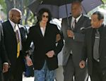 ORG XMIT: 024501_1.tif ** FOR USE AS DESIRED WITH YEAR END--FILE **Michael Jackson, center, is supported by his security personnel as he walks into the courthouse with his father Joe Jackson, right, after arriving late at Santa Barbara County Superior Court, in this March 10, 2005, file photo, in Santa Maria, Calif. (AP Photo/Kimberly White, Pool/FILE)