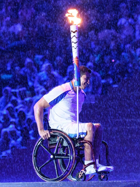 TOPSHOT - Brazilian swimmer Clodoaldo Silva holds the Paralympic torch to light the Paralympic cauldron during the opening ceremony of the Rio 2016 Paralympic Games at the Maracana stadium in Rio de J