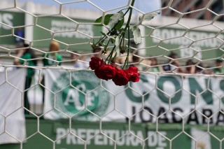 Flowers hang from a soccer net at the Arena Conda stadium where fans of the Brazilian soccer team Chapecoense began gathering, in Chapeco, Brazil, Tuesday, Nov. 29, 2016. A chartered plane that was carrying the Brazilian soccer team to the biggest match of its history crashed into a Colombian hillside and broke into pieces, Colombian officials said Tuesday. (AP Photo/Andre Penner) ORG XMIT: XAP117