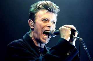 British Pop Star David Bowie screams into the microphone as he performs on stage during his concert in Vienna