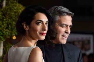 (FILES) This file photo taken on February 2, 2016 shows actor George Clooney and his wife Amal Clooney arriving at The Universal Premiere of Hail, Caesar! at the Regency Village Theatre, in Westwood, California. Lebanese-British human rights lawyer Amal Alamuddin Clooney and wife of American actor George Clooney is pregnant with twins, a family friend said on Februaru 8, 2017. / AFP PHOTO / Valerie Macon