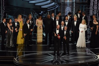'La La Land' producer Jordan Horowitz (C) speaks while holing an oscar and the winner card before reading the actual Best Picture winner 'Moonlight' onstage during the 89th Oscars on February 26, 2017 in Hollywood, California. / AFP PHOTO / Mark RALSTON