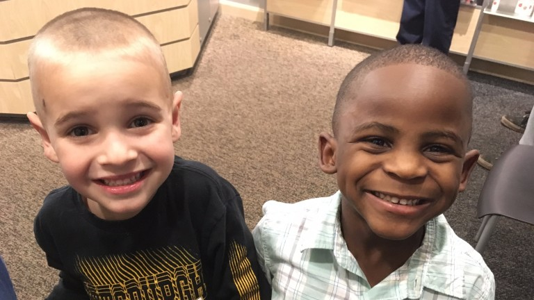 In this Feb. 28, 2017, photo, 5-year-olds Jax, left, and Reddy smile after Jax got a haircut similar to his friend's at the Great Clips in Louisville, Ky. The story about the two boys and their racial