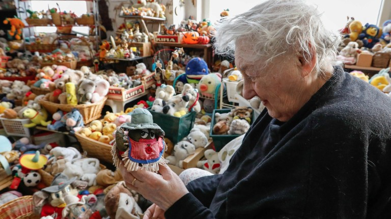 "Belgian Catherine Bloemen, 86, poses with her ""singing cactus"" stuffed toy among a collection of more than 20,000 pieces she is collecting for more than 65 years, in her house in Brussels"
