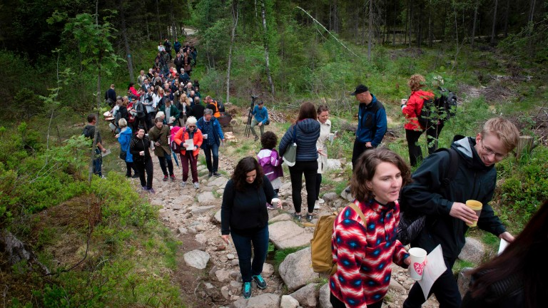 (FILES) This Handout photo made available by Bjorvika Utvikling shows people making their way to a small clearing in a forest on the outskirts of Oslo on June 2, 2017 to bring this year's manuscript b