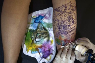 A tattoo artist makes a tattoo on the leg of a woman during the Tattoo Week in Sao Paulo, Brazil, July 14, 2017. / AFP PHOTO / Miguel SCHINCARIOL