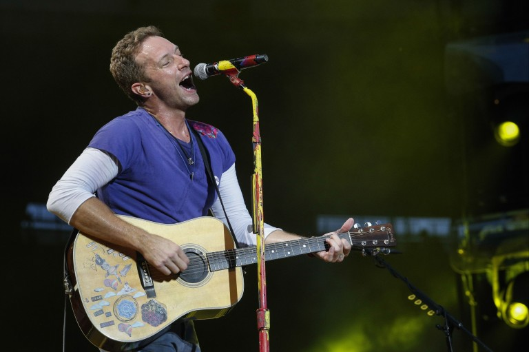 Lead singer of British band Coldplay Chris Martin performs at the Stade de France Arena in Saint Denis, on the outskirts of Paris, on July 15, 2017.  / AFP PHOTO / GEOFFROY VAN DER HASSELT / RESTRICTE