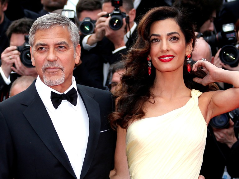 "FILE PHOTO: George Clooney and his wife Amal pose on the red carpet as they arrive for the screening of the film ""Money Monster"" during the 69th Cannes Film Festival in Cannes, France"