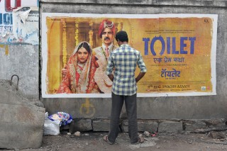 An Indian man urinates on a wall on the roadside in front of a poster for the Hindi film
