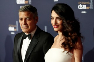 FILE PHOTO: Actor George Clooney and his wife Amal pose as they arrive at the 42nd Cesar Awards ceremony in Paris, France, February 24, 2017. REUTERS/Gonzalo Fuentes/File Photo ORG XMIT: TOR240