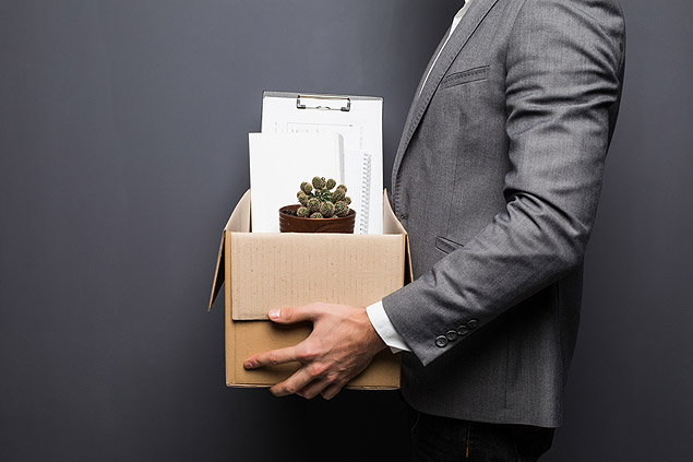 Fired man employee hiding behind box with personal items