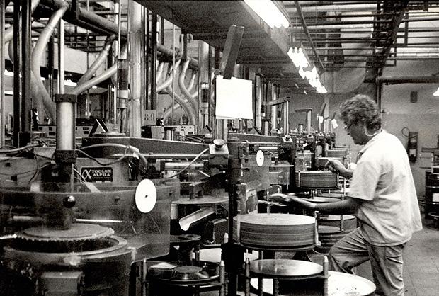 Funcionário opera prensas automáticas em fábrica de discos