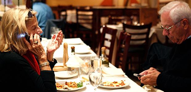 Casal usa celular em restaurante