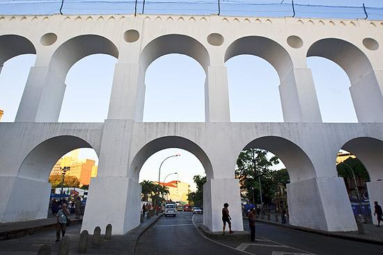 Pessoas caminham junto aos Arcos da Lapa, que acabam de passar reformas no centro do Rio