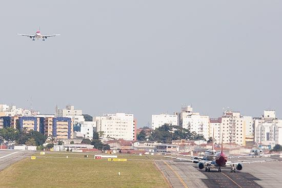 Avião aterissa no aeroporto de Congonhas, em são Paulo, enquanto outros três fazem fila para decolar