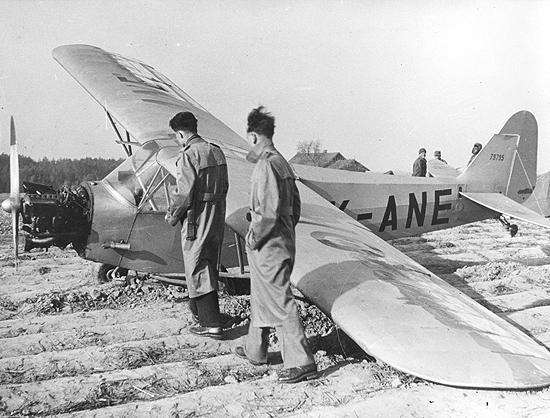 Foto de 1953 de Jiri Wertheimer e Zdenek Volf (à dir.) olhando o avião recém-pousado no qual fugiram