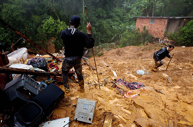 Moradores buscam por desaparecidos após chuva provocar deslizamento de terra na região serrana do Rio