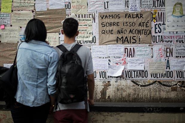 Casal diante de cartazes contra viol�ncia sexual em tapume no Masp