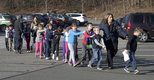 Policiais levam crianças da Sandy Hook Elementary School em fila, em Newtown, em Connecticut (EUA). Escola que sofreu massacre pelo jovem Adam Lanza. *** FILE - In this Dec. 14, 2012 file photo provided by the Newtown Bee, Connecticut State Police lead a line of children from the Sandy Hook Elementary School in Newtown, Conn., where gunman Adam Lanza opened fire, killing 26 people, including 20 children. (AP Photo/Newtown Bee, Shannon Hicks, File) MANDATORY CREDIT: NEWTOWN BEE, SHANNON HICKS ORG XMIT: BX802