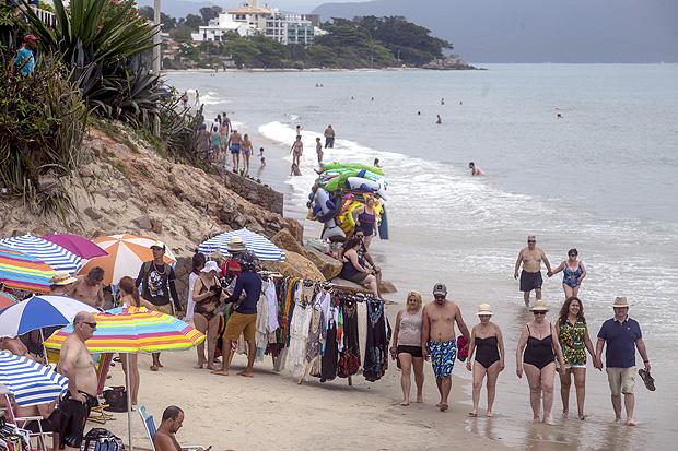 Turistas e ambulantes dividem o pequeno espaço de areia em Canasvieiras