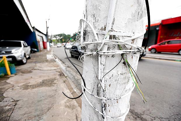 Fio preso ao poste, que foi até pintado de branco por cima, na região de São Mateus, na zona leste