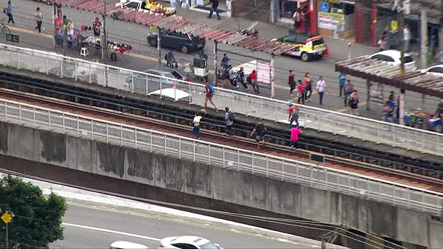 Passageiros caminham nos trilhos após falha em sistema de controle de trens na linha 5-lilás