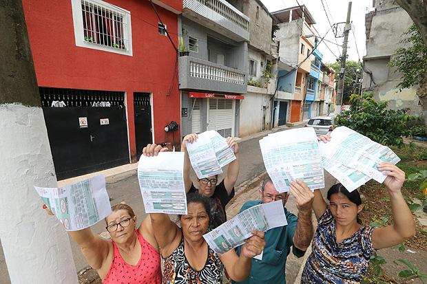 Moradoras do conjunto Promorar, no Jardim São Luís, mostram cobrança de IPTU feita pela prefeitura