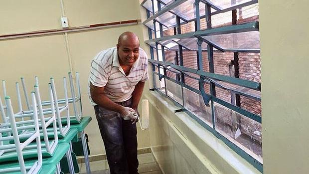 Manutenção da escola é feita com a ajuda da comunidade; acima Diego Lima pintando parede