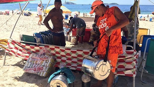 A rotina dos vendedores de mate nas praias do Rio, sob calor de 40º e com 50 kg nas costas --- Na praia, Souza armazena uma parte do mate em uma barraca e sai para a venda com 5 litros no galão cheio de gelo; quando acaba, ele volta até a barraca para reabastecer | Foto: Renata Mendonça/BBC