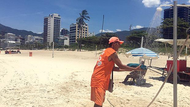 A rotina dos vendedores de mate nas praias do Rio, sob calor de 40º e com 50 kg nas costas --- O refresco do vendedor é molhar a toalha na ducha e colocá-la geladinha nas costas | Foto: Renata Mendonça/BBC