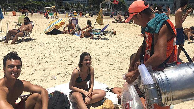 A rotina dos vendedores de mate nas praias do Rio, sob calor de 40º e com 50 kg nas costas --- Estratégia do vendedor também é chegar de forma descontraída para ganhar novos clientes - além de nunca negar o famoso 'chorinho' | Foto: Renata Mendonça/BBC