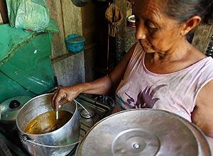 Maria Alberta do Nascimento prepara peixe em Barcelos, AM