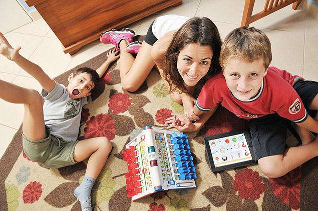 Mãe com dois filhos, um brincando com Cara-a-Cara e outro usando o iPad.