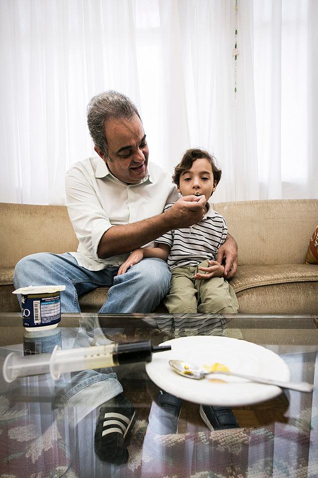 O médico Leandro Cruz Ramires Silva, 50, trata o filho Ben'ício, 6, com pasta de canabidiol (CBD) misturada ao iogurte