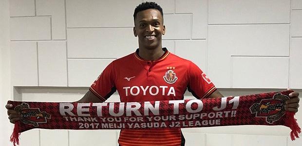 Jô posa com a camisa do Nagoya Grampus em sua chegada ao Japão