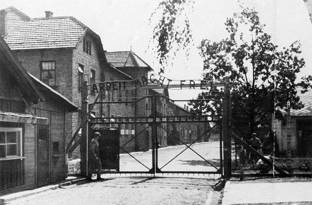 """Vista de portão do campo de concentração de Auschwitz, na Alemanha, no qual se lê """"Arbeit macht frei"""" (O Trabalho Liberta], slogan nazista."""